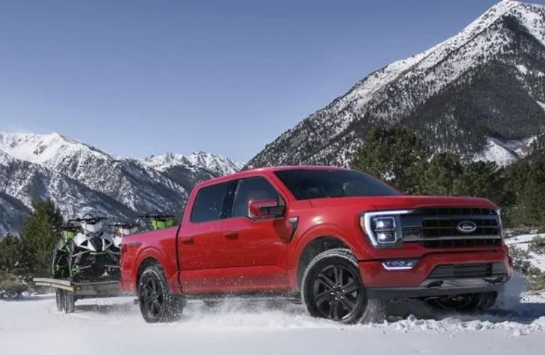 Red 2021 Ford F-150 on a snowy mountain land.