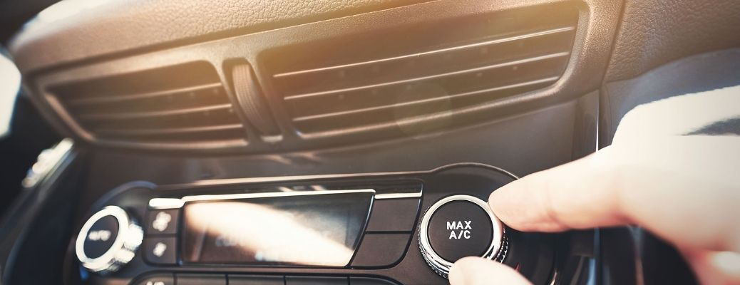 man's hand on the car air conditioning knob