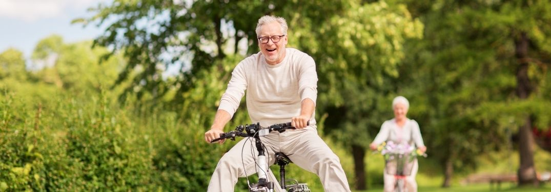 Old couple riding a bike in a park