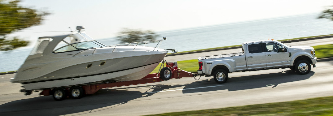 white 2018 Ford Super Duty towing a boat near water