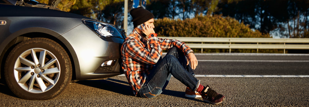 man sitting in front of broken down car on side of road on phone