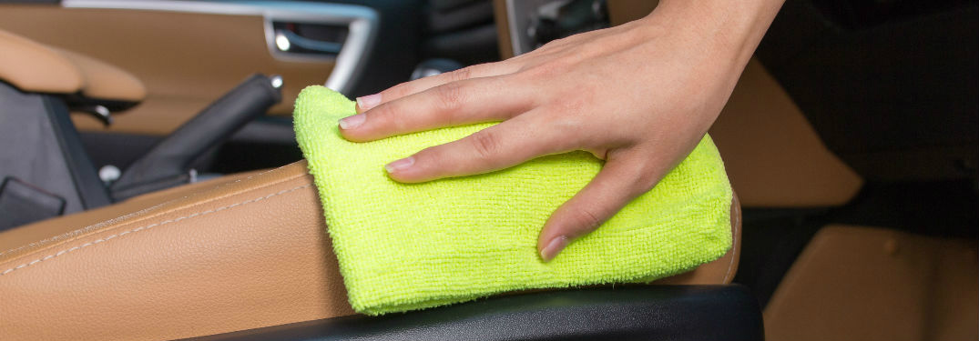 woman's hand wiping down leather seats