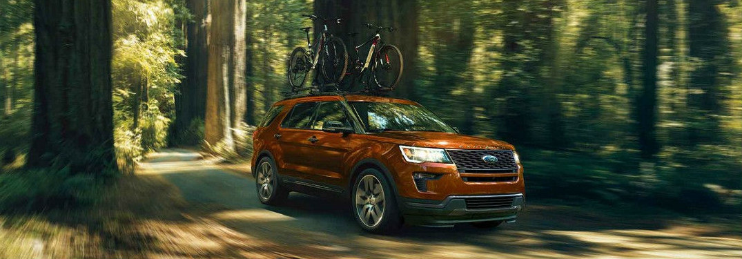 2018 Ford Explorer driving through forest with bikes on its roof
