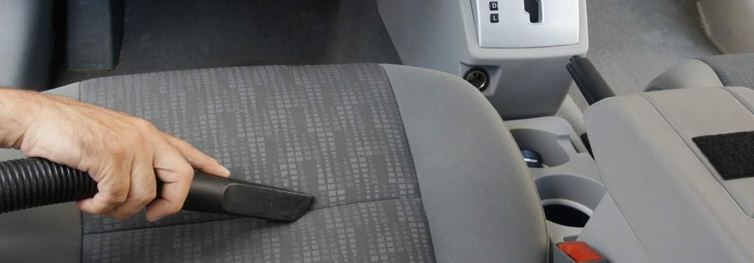 vacuuming the driver's seat of a car