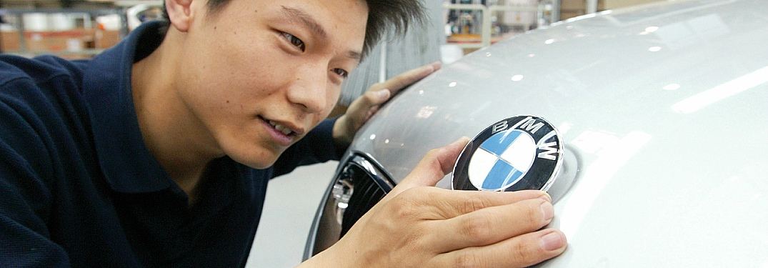 Man putting BMW emblem on the hood of a car