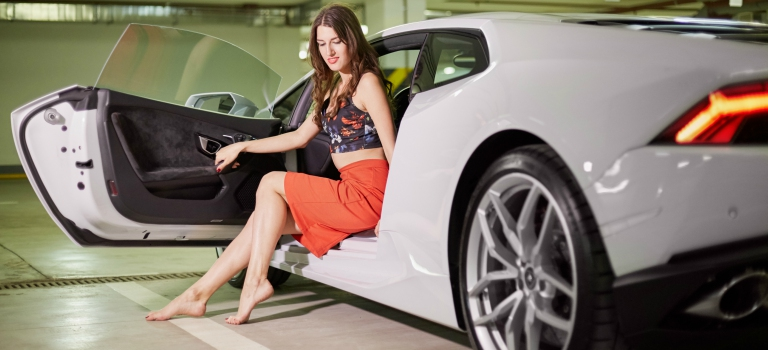 Woman getting out of a white supercar