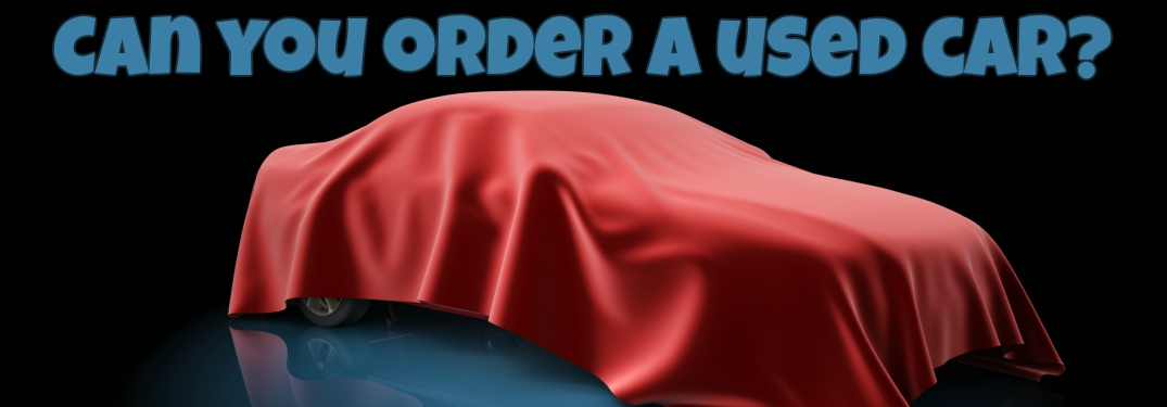 unknown car under a red cover with can you order a used car text