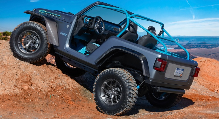 Custom lifted Jeep Wrangler gray climbing a hill side view