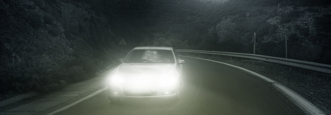 car driving at night on a road with bright headlights