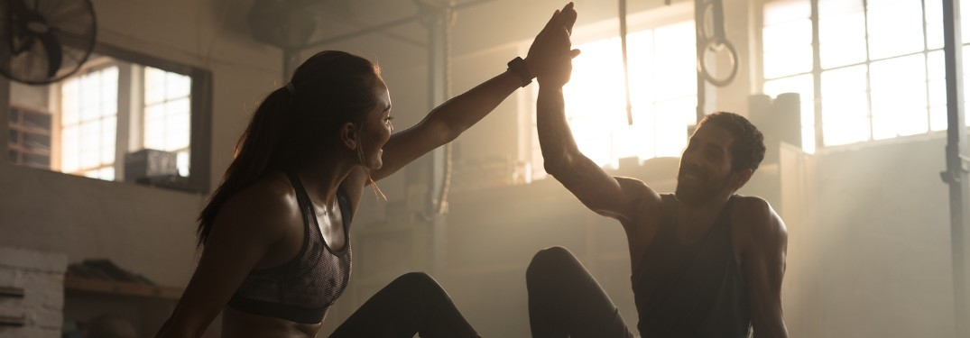 Man and woman high-fiving in gym after workout