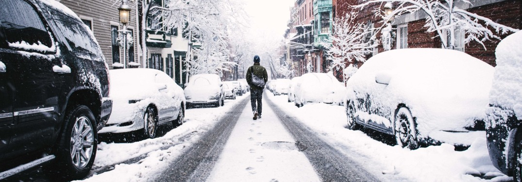 Man walking down snowy street flanked by cars