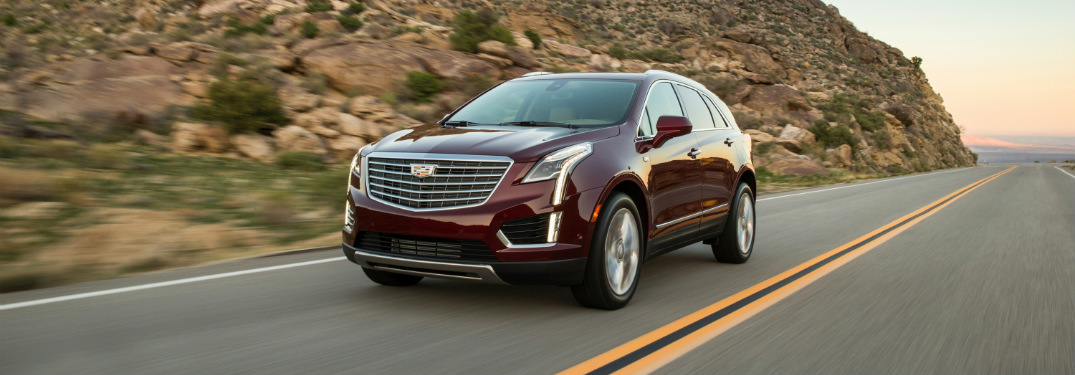 red 2018 cadillac xt5 driving on highway with desert mountains in background