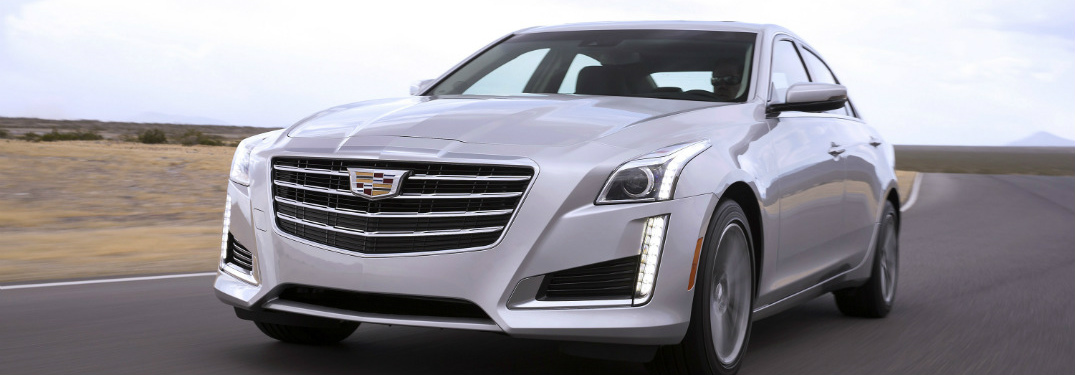 white 2018 cadillac cts sedan driving on open road