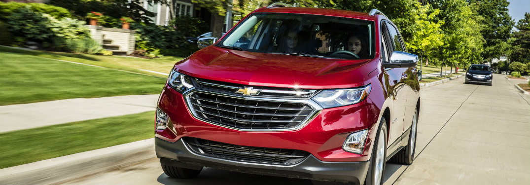red 2018 chevy equinox driving on suburban road