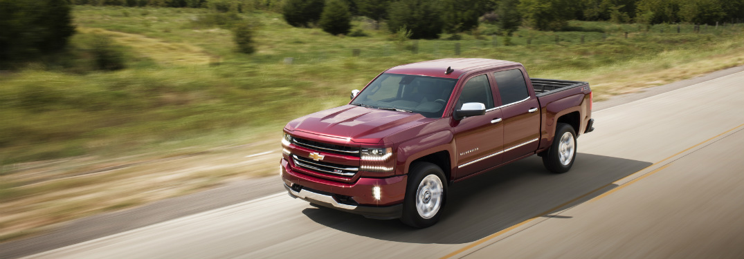 red 2018 chevrolet silverado 1500 driving on country highway