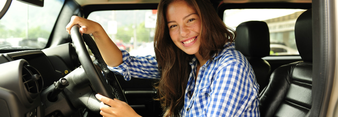 young woman in driver seat of vehicle