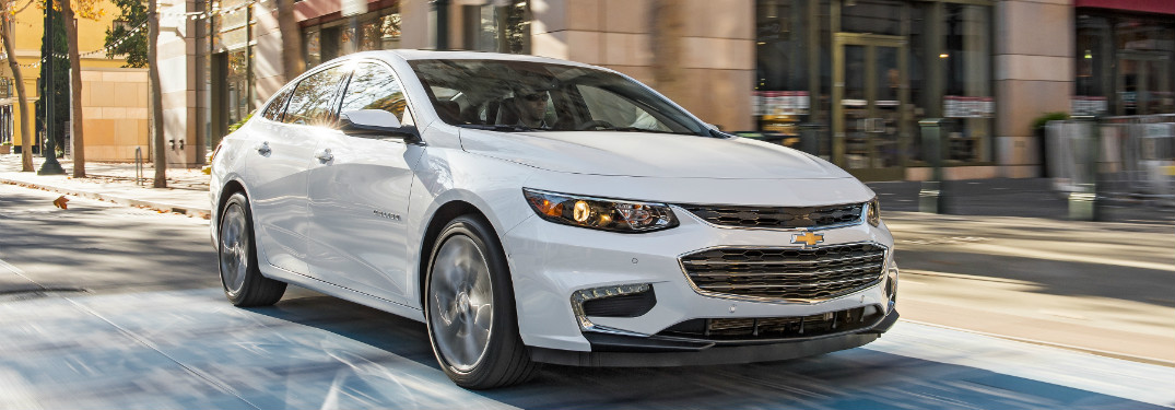 white 2018 chevrolet malibu driving through daytime city streets