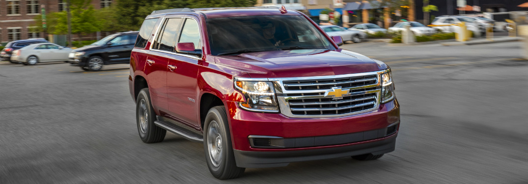 red 2018 chevrolet tahoe driving through parking lot in downtown area