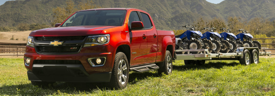 red 2018 chevrolet colorado towing trailer of multiple four-wheelers