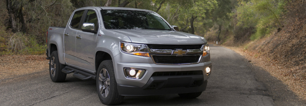 silver 2018 chevrolet colorado on paved trail in forest