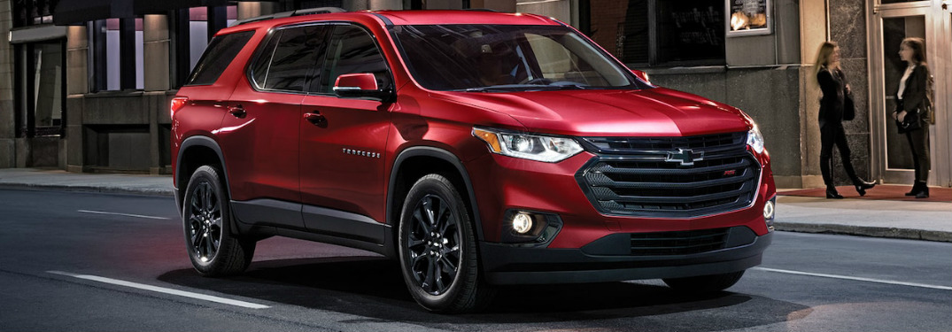 front and side view of red 2019 chevrolet traverse driving on city street
