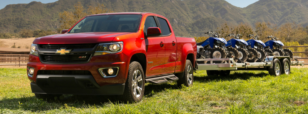 front and side view of red 2019 chevy colorado towing trailer with atvs on it