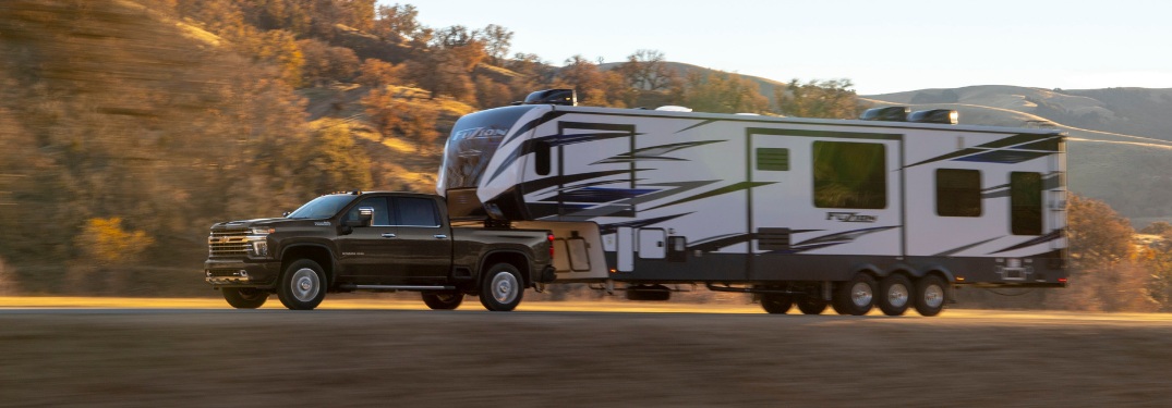 side view of black 2020 chevy silverado hd towing large camping trailer