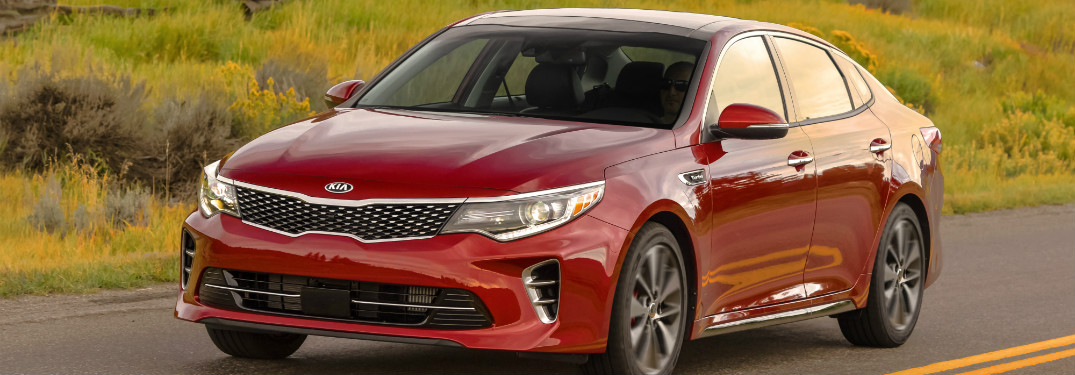 red 2018 kia optima driving on highway