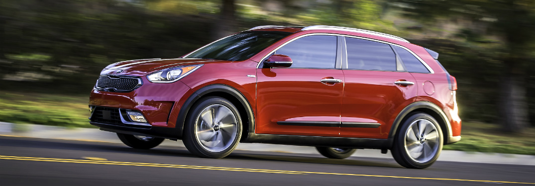 side view of red 2018 kia niro driving on road