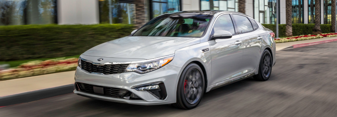white 2019 kia optima parked on street in city