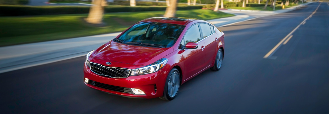 red 2018 kia forte driving on road
