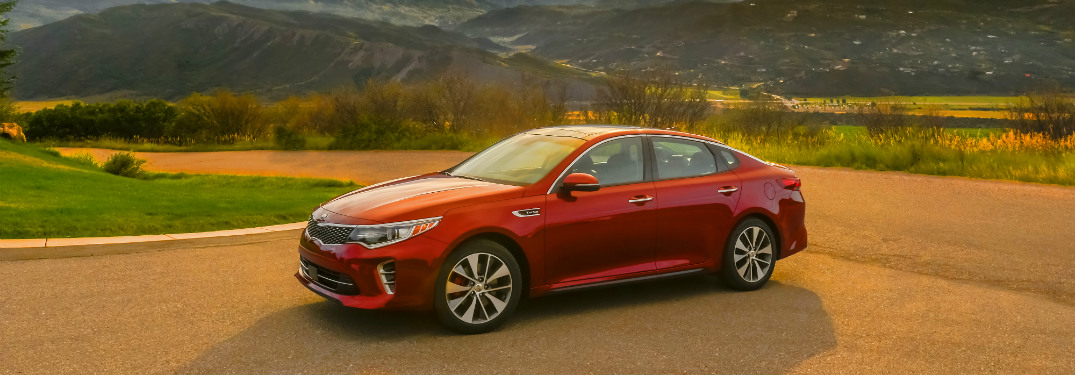 red 2018 kia optima on road with grass hills behind it