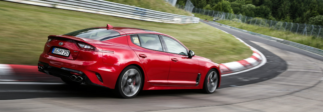 rear view of red 2018 kia stinger going around bend on professional race course