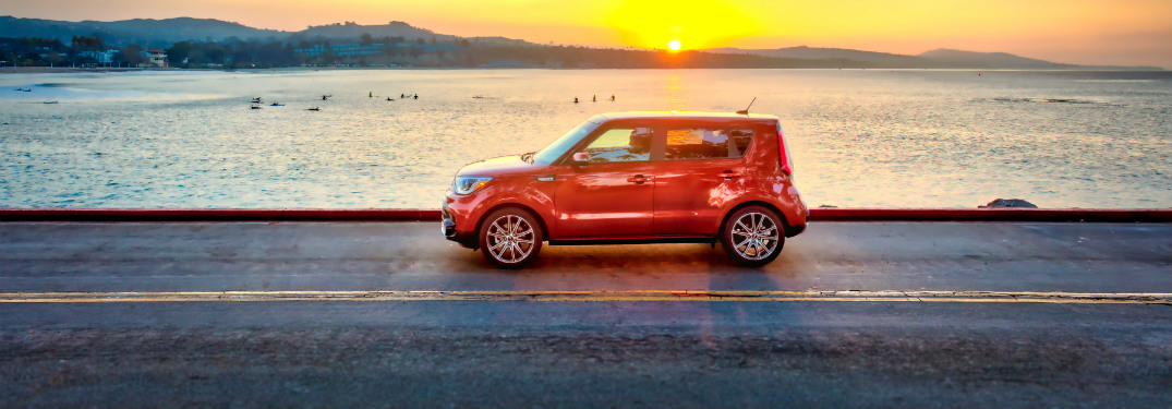side view of orange 2019 kia soul driving down road with ocean and sun behind it