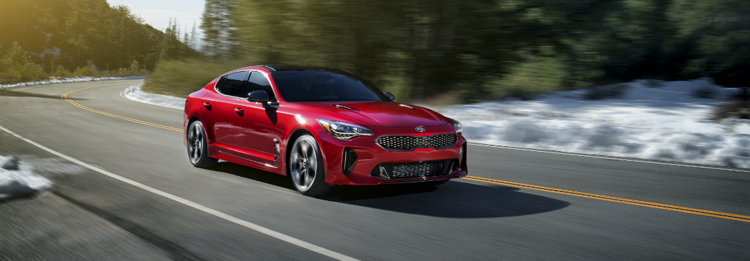 red 2018 kia stinger driving on empty road with trees and snow around it