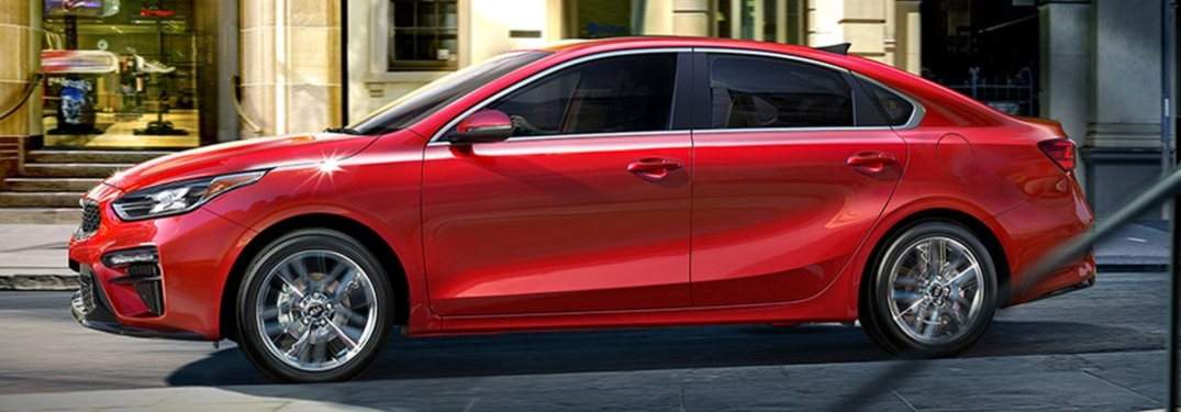 Side view of a red 2019 Kia Forte in the city