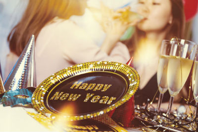 black and gold happy new year plate with girls toasting champagne in background