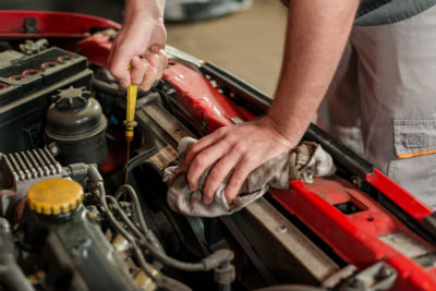 man pulling out dipstick to check levels of engine oil