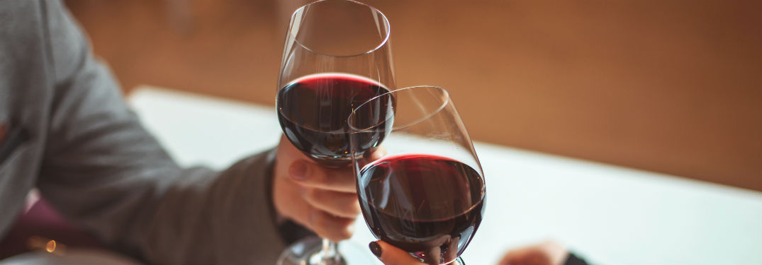 two people tapping their wine glasses together filled with red wine