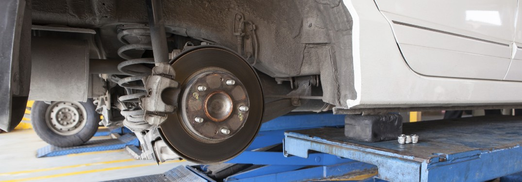 car on lift with tire off and brake rotor exposed