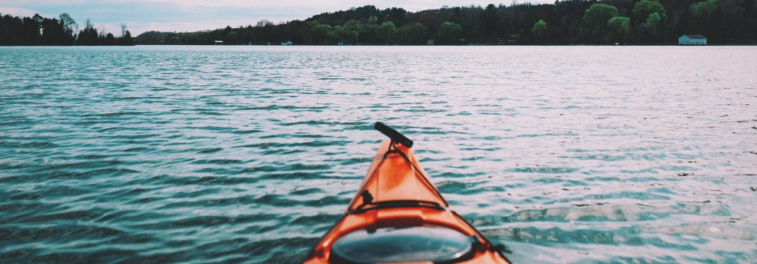 front end of kayak in lake with trees in distance