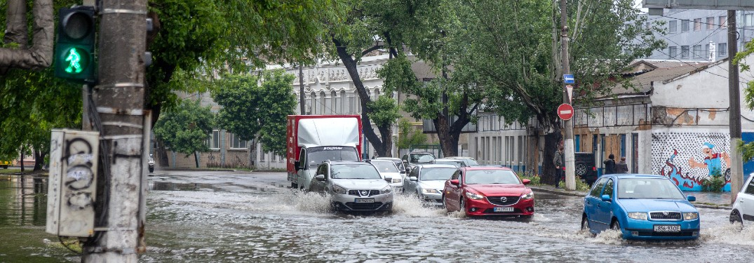 group of cars driving through a flooded city street