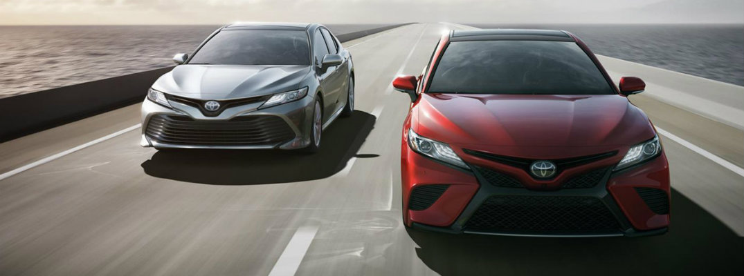 Silver and red Toyota Camry models driving side by side down highway road