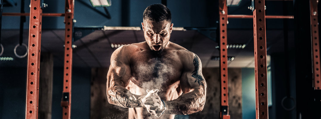 Man at gym powdering hands in preparation of doing pull-ups