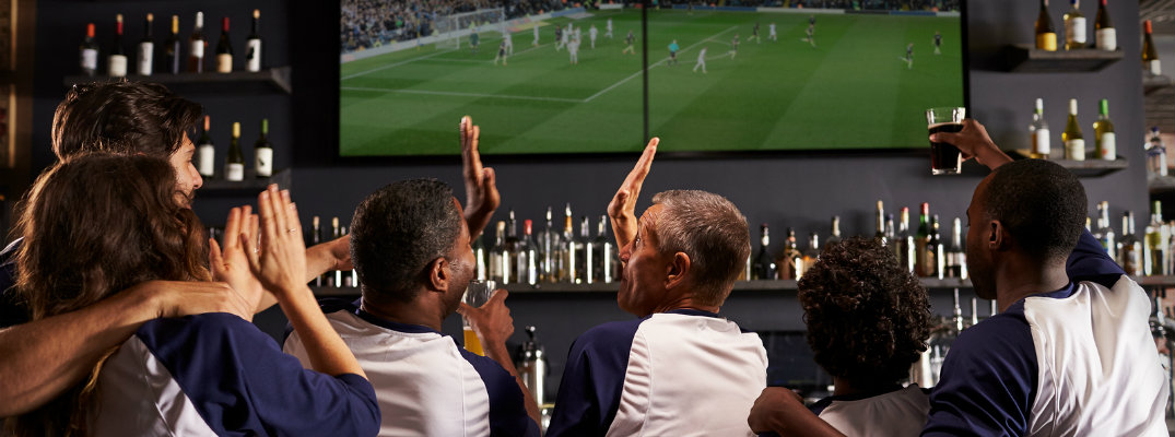 Group of friends in matching blue and white baseball shirts cheering and high fiving while watching soccer in a sports bar