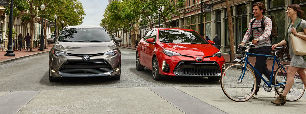 Two people with their bikes walking in front of two 2018 Toyota Corolla models