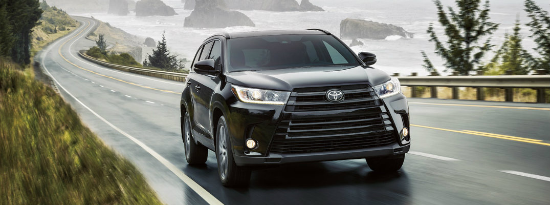 Black 2018 Toyota Highlander driving on wet waterfront road with jagged rocks in background coming out of water