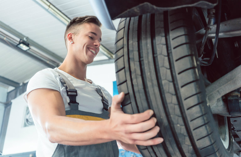 Man putting a tire onto a car in an auto body shop