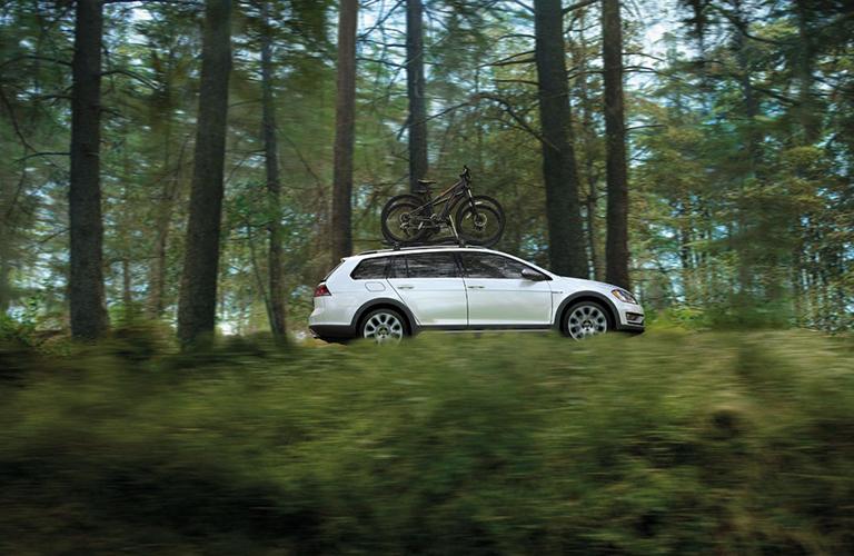 White 2018 Volkswagen Golf Alltrack driving through the woods
