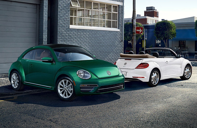 Green and white 2018 Volkswagen Beetle models parked next to eachother